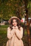 Le portrait d'un chapeau de port de fille et le manteau en automne se garent Photographie stock libre de droits