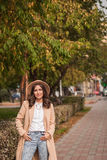 Le portrait d'un chapeau de port de fille et le manteau en automne se garent Photos libres de droits