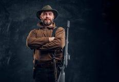 Le portrait d'un chasseur barbu avec le fusil posant avec ses bras a crois? Photo de studio sur un fond fonc? de mur photographie stock libre de droits
