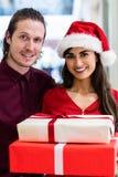 Le portrait d'un couple dans Noël attire la position avec des cadeaux de Noël Photographie stock