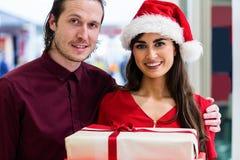 Le portrait d'un couple dans Noël attire la position avec des cadeaux de Noël Photos libres de droits