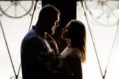 Le portrait d'un couple romantique dans un contre-jour d'une fenêtre ou font Images stock