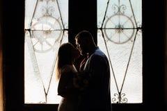 Le portrait d'un couple romantique dans un contre-jour d'une fenêtre ou font Image stock