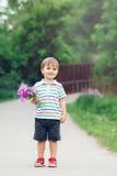 Le portrait d'un enfant en bas âge drôle mignon de petit garçon se tenant dans le pré de champ de forêt avec le pissenlit fleurit Images stock