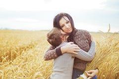 Le portrait d'un fils embrasse sa mère sur un champ Image stock