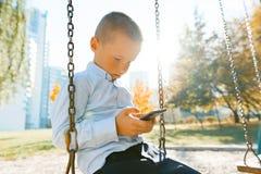 Le portrait d'un garçon de sourire 6, 7 années, enfant monte une oscillation en parc d'automne, heure d'or photographie stock