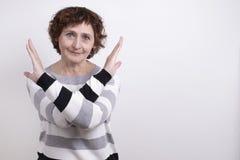 Le portrait d'un geste de femme d'âge, croisé devant lui refuse de communiquer photo stock
