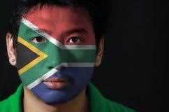Le portrait d'un homme avec le drapeau de l'Afrique du Sud a peint sur son visage sur le fond noir images stock