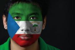 Le portrait d'un homme avec le drapeau de la Guinée équatoriale a peint sur son visage sur le fond noir photo libre de droits