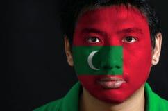 Le portrait d'un homme avec le drapeau des Maldives a peint sur son visage sur le fond noir photos stock