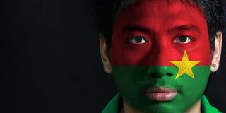 Le portrait d'un homme avec le drapeau du Burkina Faso a peint sur son visage sur le fond noir photos stock