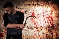 Le portrait d'un homme tenant une lame tenant le sang proche a souillé le wa images stock