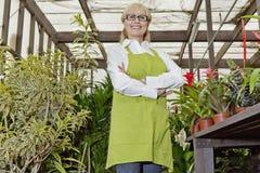 Le portrait d'un jardinier féminin heureux se tenant avec des bras a croisé dans le jardin botanique photographie stock libre de droits