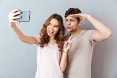 Le portrait d'un jeune couple heureux montrant la paix font des gestes Photographie stock libre de droits