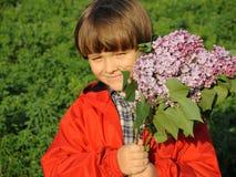 Le portrait d'un jeune garçon de sourire avec le lilas dans le sien remet 1 Photo stock