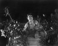 Le portrait d'un jeune homme s'asseyant sur un mur avec s'abaisse et des usines et sourire (toutes les personnes représentées ne  image libre de droits