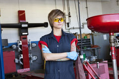 Le portrait d'un jeune mécanicien féminin utilisant la vitesse protectrice avec des bras a croisé dans l'atelier Images libres de droits