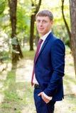 Le portrait d'un jeune marié dans un costume bleu et un lien rouge à un mariage marchent Photographie stock