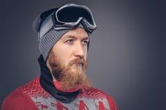 Le portrait d'un mâle barbu roux brutal dans un chapeau d'hiver avec les verres protecteurs s'est habillé dans un chandail rouge, image stock