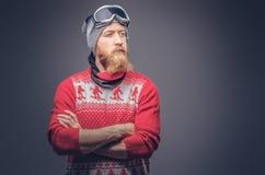 Le portrait d'un mâle barbu roux brutal dans un chapeau d'hiver avec les verres protecteurs s'est habillé dans un chandail rouge, images stock