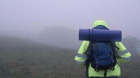 Le portrait d'un touriste d'homme dans le hoodie de gilet de signal avec un sac à dos est un dans le brouillard dans les montagne clips vidéos