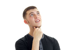 Le portrait d'un type étonnant qui a soulevé le regard garde votre main près de votre menton et sourire Photographie stock