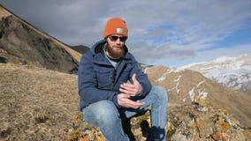 Le portrait d'un voyageur barbu dans les lunettes de soleil et un chapeau se repose sur une roche contre le contexte des montagne banque de vidéos