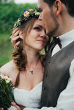 Le portrait d'une étreinte de jeunes mariés sur le fond quitte la forêt Photo libre de droits