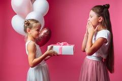 Le portrait d'une adolescente sur un fond rose, avec des cadeaux, le concept d'anniversaire, un donne à une autre fille un cadeau photo stock