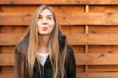 Le portrait d'une belle fille au sujet de quelque chose rêve Sur le fond en bois Photo libre de droits