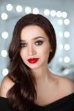 Le portrait d'une belle fille avec les lèvres rouges lumineuses et de beaux cheveux contre un bokeh de fond s'allume dans le salo Photographie stock
