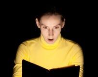 Livre magique rougeoyant de lecture de jeune femme Photographie stock