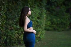 Le portrait d'une belle jeune femme caucasienne dans des blues-jean et le denim complètent, peau propre, longs cheveux et maquill photos libres de droits