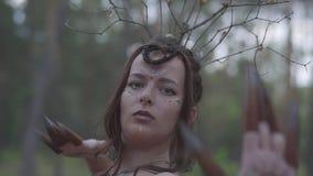 Le portrait d'une fée attirante de dryade ou de forêt avec une guirlande des branches sur la tête et a peint le troisième oeil su clips vidéos