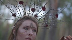 Le portrait d'une fée attirante de dryade ou de forêt avec une guirlande des branches sur la tête et a peint le troisième oeil su banque de vidéos