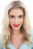 Le portrait d'une femme blonde de sourire dans la robe bleue regardant est venu photographie stock