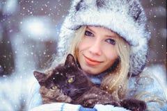 Le portrait d'une femme fascinante douce dans un chapeau d'hiver avec un catsnow tombe dans les tons froids, amour des animaux Images stock