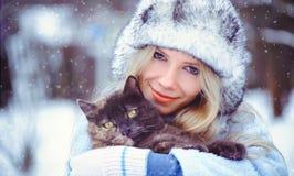 Le portrait d'une femme fascinante douce dans un chapeau d'hiver avec un catsnow tombe dans les tons froids, amour des animaux Photo stock