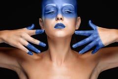 Le portrait d'une femme qui pose a couvert de peinture bleue image stock