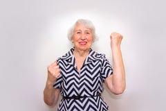 Le portrait d'une femme supérieure gaie faisant des gestes la victoire sur le rose Photos stock