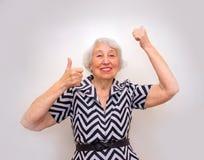 Le portrait d'une femme supérieure gaie faisant des gestes la victoire sur le rose Photographie stock