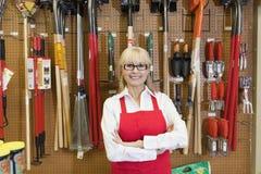 Le portrait d'une femme supérieure heureuse avec des bras a croisé devant l'outil de jardinage Image libre de droits