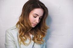 Le portrait d'une fille avec l'écoulement se courbe avec les yeux fermés sur un fond blanc Photo libre de droits