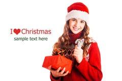 Le portrait d'une fille dans Noël vêtx avec un cadeau à disposition sur le fond blanc d'isolement photographie stock libre de droits