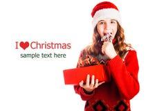 Le portrait d'une fille dans Noël vêtx avec un cadeau à disposition sur le fond blanc d'isolement photo stock