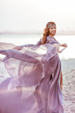 Le portrait d'une fille dans une robe de quirlande électrique marche Image stock