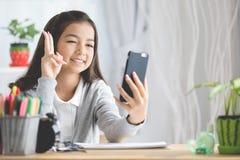 Le portrait d'une fille de sourire dirigeant le doigt et prennent une photo par m images stock
