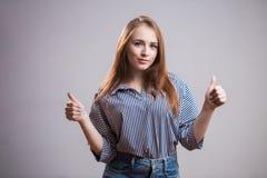 Le portrait d'une fille joyeuse montrant des pouces vers le haut du geste deux remet le fond gris avec l'espace de copie Une bell photographie stock