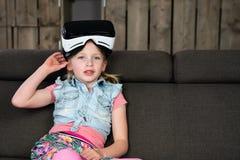 Le portrait d'une fille, a plaisir à l'aide d'un casque de réalité virtuelle à la maison image stock