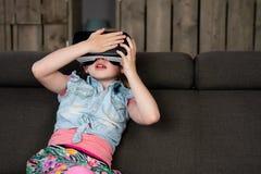 Le portrait d'une fille, a plaisir ? l'aide d'un casque de r?alit? virtuelle ? la maison photo stock